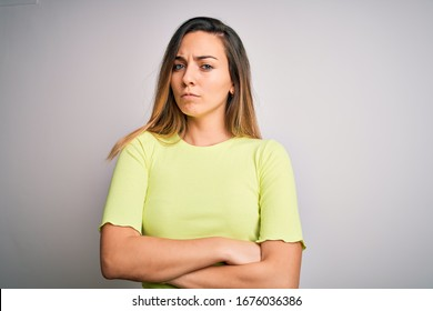 Beautiful blonde woman with blue eyes wearing green casual t-shirt over white background skeptic and nervous, disapproving expression on face with crossed arms. Negative person.
