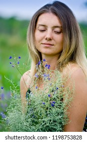 Beautiful blonde woman with a bouquet of sagebrush looks down