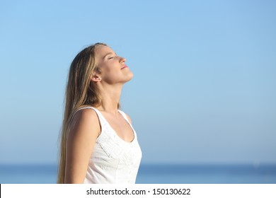 Beautiful blonde woman breathing happy with the blue sky in the background