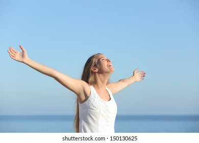 Beautiful blonde woman breathing happy with raised arms with the sky in the background