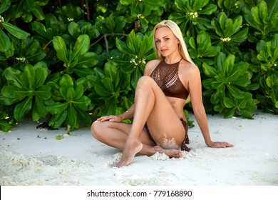 Beautiful blonde woman in the brown knitted bikini sitting on the lonely beach near green bushes and white sand in the shadow. Zanzibar. Nungwi.