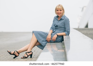 Beautiful blonde woman  in a checkered blue and white dress sitting on marble smiling.  business woman concept