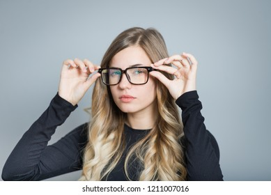 beautiful blonde woman curious adjusts glasses, isolated over black background