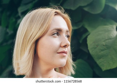 Beautiful blonde woman with curly short bob hairstyle. Fashion sensual posing on summer sunset. Portrait of a cute girl in the garden. Blonde with short hair and red lips.