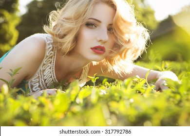 Beautiful blonde woman with curly short bob hairstyle, delicate make up and red lips in green short dress at the park. Fashion sensual posing on summer sunset. Outdoors