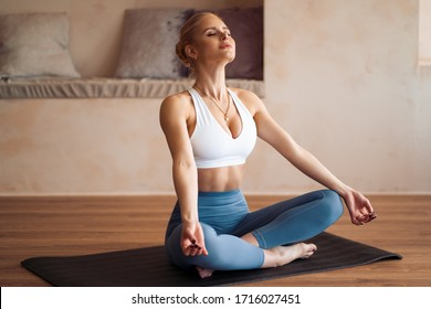 Beautiful blonde woman doing home workout indoors. Woman practice yoga at home. Fit girl using workout tutorials for healthy active lifestyle. Woman using quarantine for home workouts. Stretching