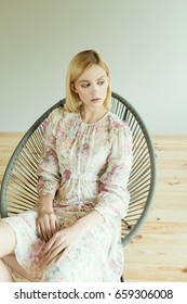Beautiful blonde woman in dress with floral print sits on a chair on a gray background.