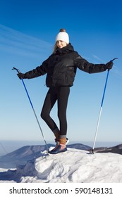 Beautiful blonde woman dressed in black warm clothes posing on the very top of a snowy mountain. She come cross-country skiing. Beautiful views and fabulous blue skies makes wonderful atmosphere.