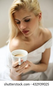 Beautiful blonde woman drinking hot coffee in bed on a summer morning. Above view.