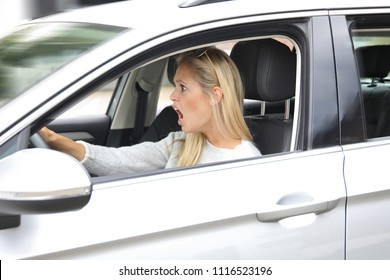 Beautiful blonde woman driving a car and looking horrified
