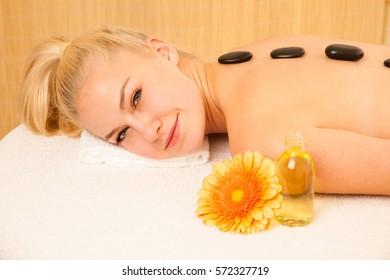 Beautiful blonde woman enjoying massage treatment in sap salon