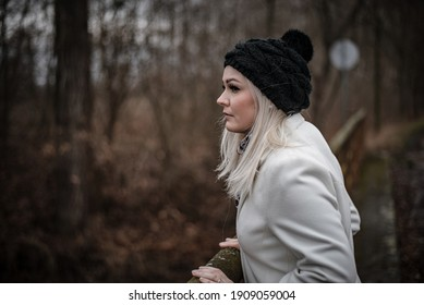 Beautiful blonde woman is enjoying view during a winter walk out of town to keep social distance