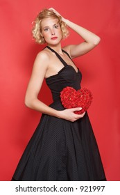 The beautiful blonde woman in an evening dress, she holds in hands heart that made of roses. Background is red