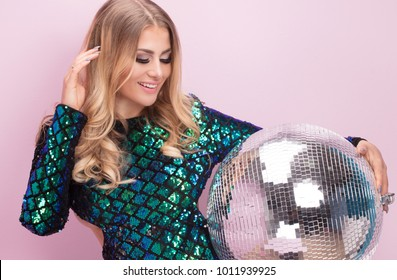 Beautiful blonde woman in fashionable party dress. Glamour style beauty portrait. Girl posing on pastel pink background holding silver disco ball.