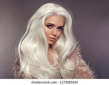 Beautiful Blonde Woman In Faux Fur Coat. Portrait Of Young Sexy Blond Model With Beauty Makeup, long white hair style, posing isolated on gray studio background. High Fashion Winter Style.