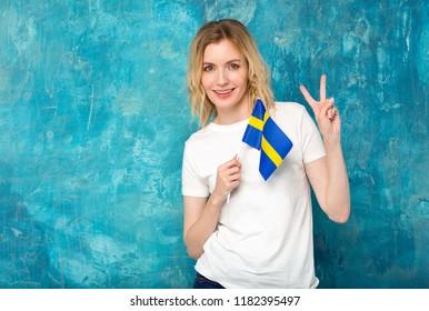 Beautiful blonde woman with the flag of Sweden. Portrait Scandinavian woman.