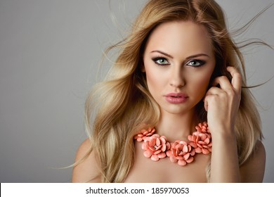 Beautiful blonde woman with flower necklace. Jewelry and Beauty. Fashion photo