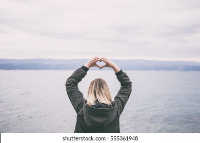 beautiful blonde woman forming a heart shape with hands on a beach. autumn fashion outfit. fashionable bomber jacket. concept of love towards nature. enough space for text, lettering and copy.