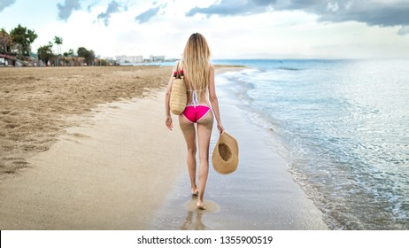 Beautiful blonde woman girl with long legs in pink bathing suit on summer beach goa