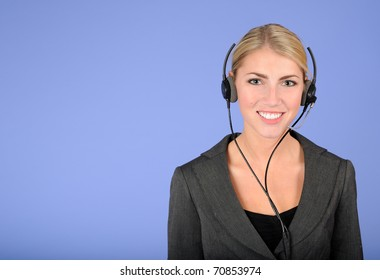 Beautiful blonde woman in gray business suit smiling as she talks on the phone through headset