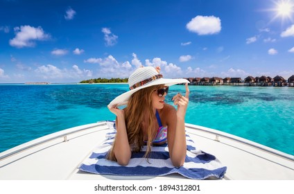 A beautiful, blonde woman with hat enjoys her summer vacation time with a sunbath on a luxury yacht over turquoise, tropical ocean in the Maldives islands
