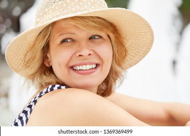 Beautiful blonde woman with hat smiling in the sun