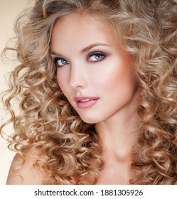 Beautiful blonde woman. Healthy Long Blond Hair. Curly Hair. Permed Hair. Afro curls. Beauty Model Girl with Luxurious Hair.