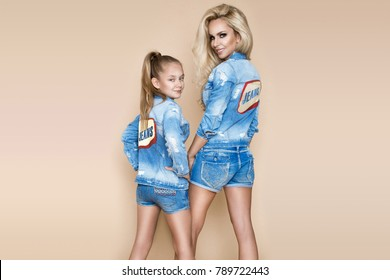 Beautiful blonde woman with her daughter in a denim jacket and shorts. Fashion models in jeans clothing.