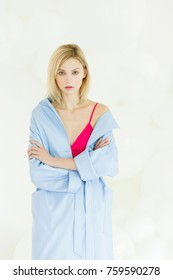 A beautiful blonde woman in her pink pants and a blue trench stands  on a white background with white balloonsl.