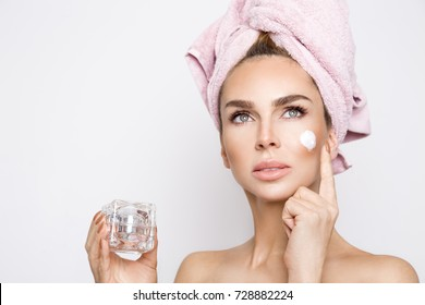 Beautiful blonde woman holding a cream in her hand and creaming her face.