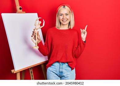 Beautiful blonde woman holding small wooden manikin smiling happy pointing with hand and finger to the side