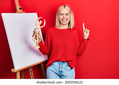 Beautiful blonde woman holding small wooden manikin smiling with an idea or question pointing finger with happy face, number one
