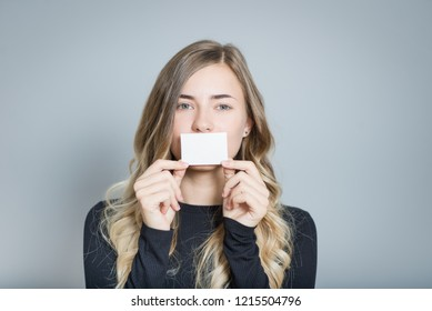 beautiful blonde woman holding a sticker in mouth, isolated over a gray background