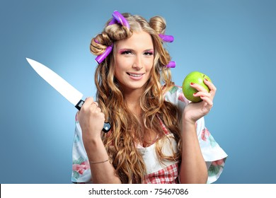 Beautiful blonde woman housewife holding apple and a knife. Studio shot over grey background.