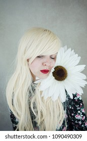 Beautiful blonde woman with a huge  daisy