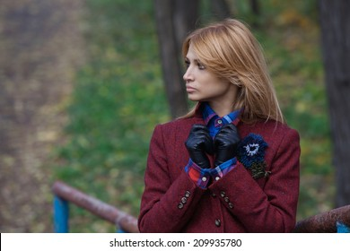 Beautiful blonde woman in jacket and leather gloves walking in autumn forest