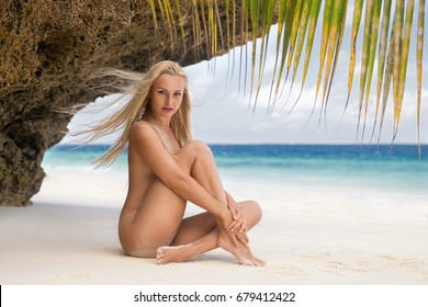 Beautiful blonde woman in the knitted brown bikini sitting on the lonely beach with turquoise water and white sand in the shadow of the palm tree leaf. Zanzibar. Nungwi.
