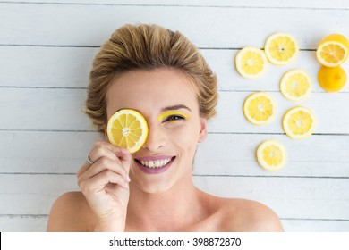 beautiful blonde woman laying on a white wooden background next to slices of lemon, having a slice of lemon on the eyes and smiling