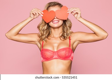 Beautiful blonde woman in lingerie with cards in the shape of a red heart in his hands on a pink background.
