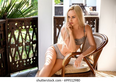 Beautiful blonde woman in lingerie sitting in the arm chair on the old African balcony in the rays of the evening sun.