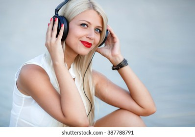 beautiful blonde woman listening to music in the city. beautiful young woman dancing with headphones hanging. woman with headphones music in the city street and smiling