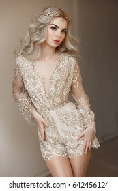 Beautiful blonde woman with long curly hair and bright makeup. Portrait of sexy young lady in elegant clothes. Romantic girl portrait.