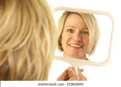 Beautiful blonde woman looking at her reflection in the mirror.  Photo is shot from the back and the focus is on her reflection.