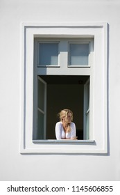 Beautiful blonde woman looks out from open window, white wall and white window frame