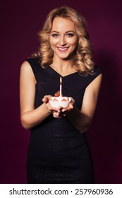 Beautiful blonde woman in luxury black dress and curly hairstyle blowing candle on birthday cake. clear skin. dark red background