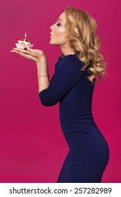 Beautiful blonde woman in luxury blue dress and curly hairstyle blowing candle on birthday cake. clear skin. pink background