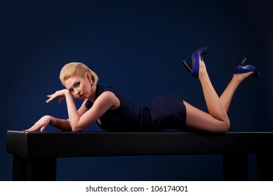 Beautiful blonde woman lying on a table, a dark background