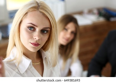 Beautiful blonde woman make some marks on screen or glass wall with silver pen. Fresh view, discuss problem, review situation, look at new angle, professional training, memo graph or chart concept