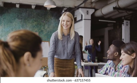 Beautiful blonde woman manager giving direction to multiethnic team. Creative business meeting at modern hipster office.