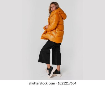 Beautiful blonde woman natural makeup wear fashion clothes casual dress code warm style total beige blouse and pants suit, big colourful warm jacket, ready for winter. studio shoot.copy space.Orange